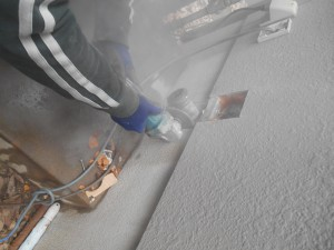 施工中:サンダーで外壁や基礎を一部カットし、既存のパイプを引き抜きます